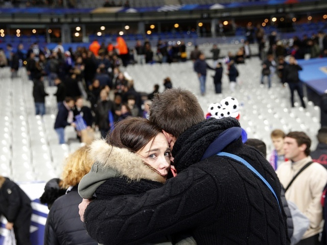 A supporter conforts a friend after invading the pitch of the Stade de France stadium at the end of the international friendly soccer match between France and Germany in Saint Denis, outside Paris, Friday, Nov. 13, 2015. Hundreds of people spilled onto the field of the Stade de France stadium after explosions were heard nearby. French President Francois Hollande says he is closing the country's borders and declaring a state of emergency after several dozen people were killed in a series of unprecedented terrorist attacks. (AP Photo/Christophe Ena)